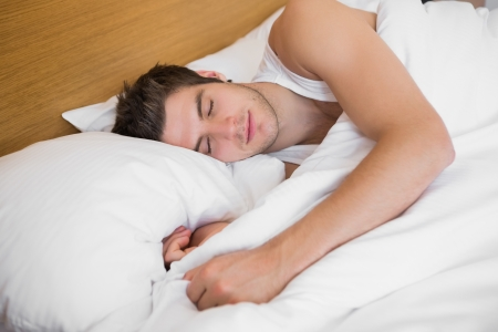Handsome male sleeping in bed in a hotel room photo