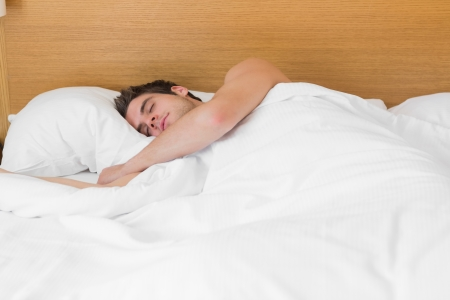 Attractive man asleep in bed in hotel room photo
