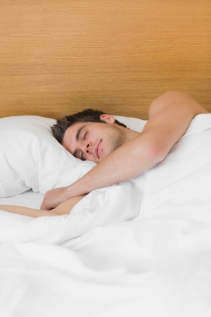 Brunette man asleep in bed in hotel room photo