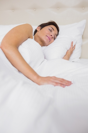Peaceful woman asleep in bed in hotel room photo