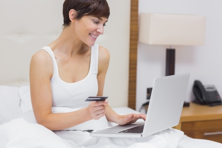 Happy woman shopping online in bed in hotel room photo