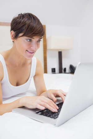 Pretty woman using laptop in bed in hotel room photo