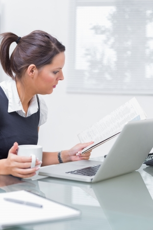 Young female executive with coffee cup and laptop reading paper at desk in office Stock Photo - 18106996