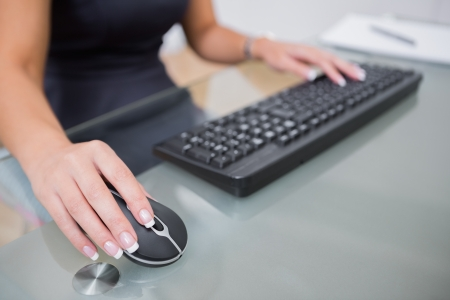 Midsection of woman using computer mouse and keyboard at office desk Stock Photo - 18107490