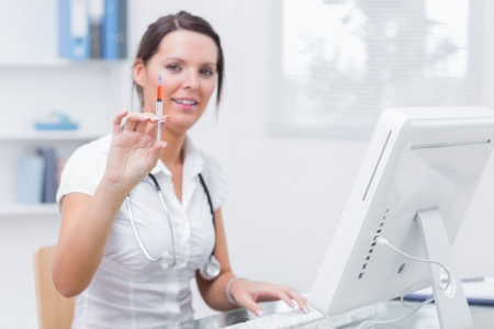 Portrait of young female doctor holding an injection in front of computer at clinic Stock Photo - 18088456