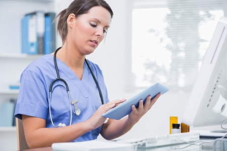 scrolling: Side view of young female surgeon using digital tablet in front of computer at desk in clinic Stock Photo