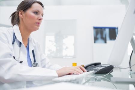 using the computer: Vista lateral del doctor de sexo femenino joven que usa el ordenador en la cl�nica