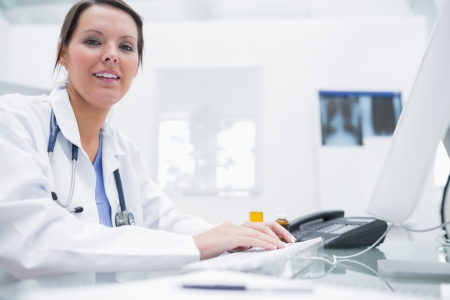 Portrait of smiling young female doctor using computer at clinic Stock Photo - 18102972