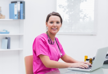 Portrait of smiling young nurse using laptop at desk in clinic photo