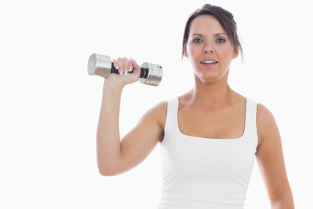 Portrait of young woman exercising with dumbbell over white background Stock Photo - 18102494