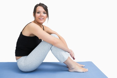 Side view of young woman in sportswear sitting on yoga mat over white background Stock Photo - 18103739