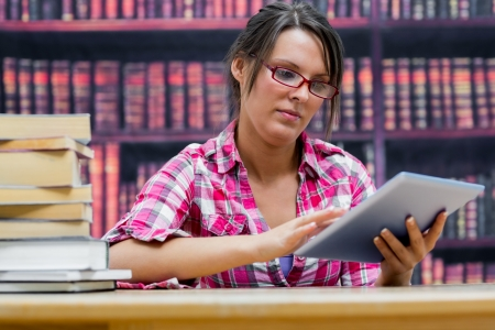 Female college student using digital tablet with stack of books at table in library photo