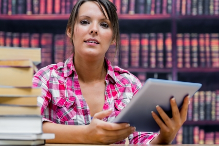 Portrait of female college student with digital tablet and stack of books at table in library photo