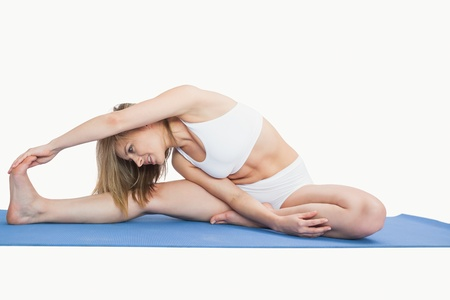 Young woman performing stretching exercise on yoga mat over white background Stock Photo - 18103740