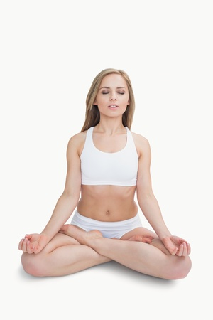 Young woman sitting in lotus position with eyes closed over white background Stock Photo - 18104901