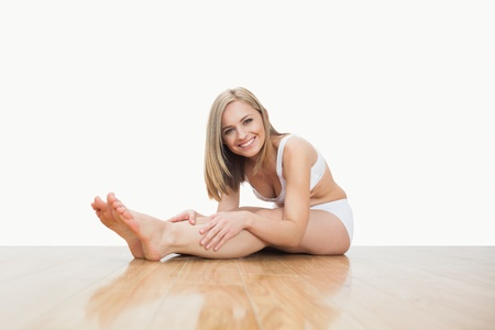 Portrait of young  woman stretching on hardwood floor over white background photo