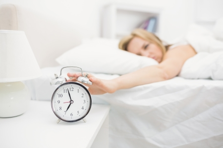 extending: Irritated young woman in bed extending hand to alarm clock at home