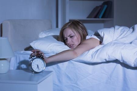despertador: Irritado mujer joven en la cama extendiendo la mano a la alarma del reloj en casa