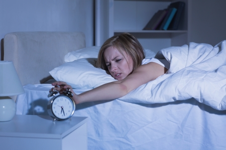 Irritated young woman in bed extending hand to alarm clock at home photo