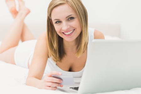 Portrait of woman doing online shopping through laptop and credit card in bed at home photo