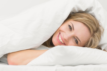 blankets: Portrait of happy beautiful young woman in bed at home