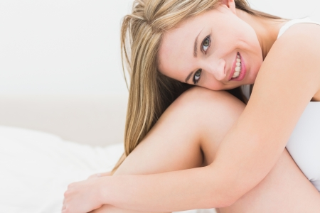 fair woman: Portrait of smiling young woman sitting in bed at home