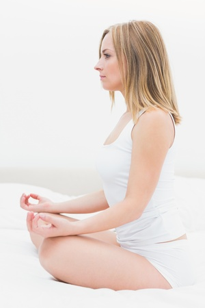 yoga pillows: Side view of young woman sitting in lotus position in bed at home