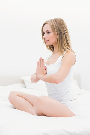 yoga pillows: Young woman sitting in praying position on bed at home