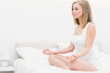 yoga pillows: Young woman sitting in lotus position on bed at home