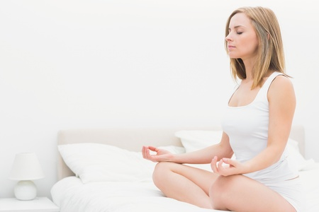 yoga pillows: Young woman sitting in lotus position with eyes on bed at home