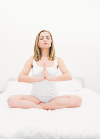 yoga pillows: Young woman sitting in praying position with eyes closed on bed at home