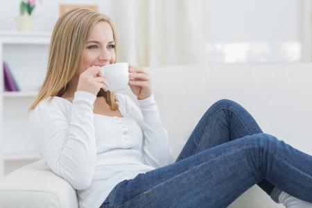 mujer tomando cafe: Mujer joven bebiendo café mientras se mira hacia otro lado en el sofá en casa