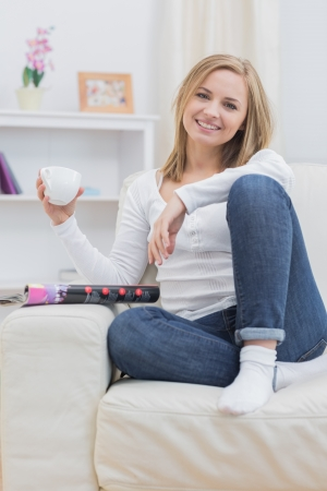 Portrait of young woman with coffee cup sitting on couch at home Stock Photo