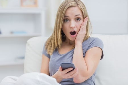 Portrait of casual shocked young woman with cellphone on sofa at home photo