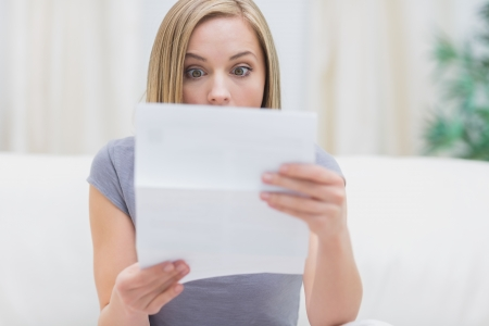 Shocked young woman reading letter in living room at home photo