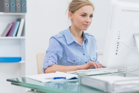 Young female executive working on computer at desk in office Stock Photo - 18108970