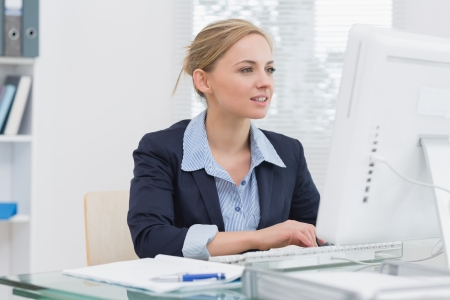 Young business woman working on computer at desk in office Stock Photo - 18108769