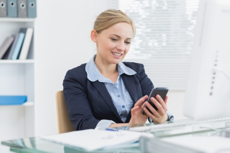 Young business woman text messaging in front of computer at office desk photo