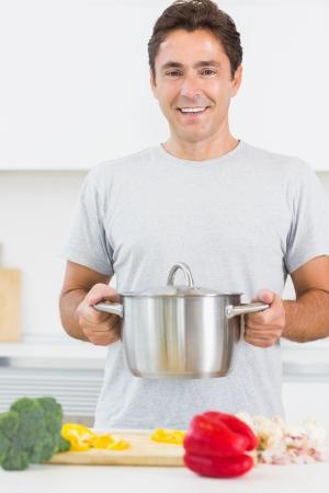 まな板: キッチンで野菜をまな板の前で大きな鍋を抱きかかえた