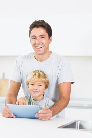 Laughing father and son using tablet in the kitchen photo