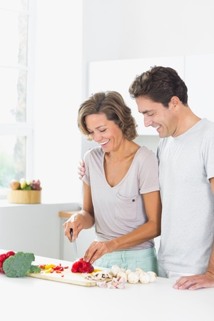 Smiling couple preparing vegetables in the kitchen photo