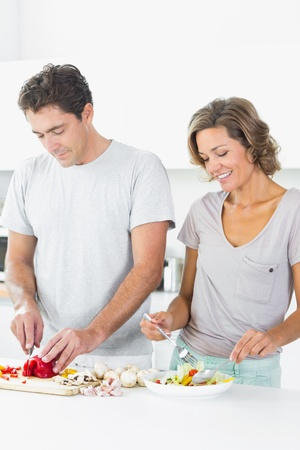 Couple preparing a salad together in kitchen photo