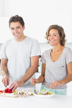 Happy couple preparing salad together in the kitchen photo