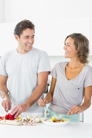 Smiling couple making salad together in the kitchen photo