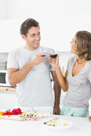 Couple toasting each other while preparing salad photo