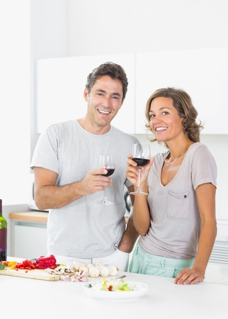 Couple drinking red wine and preparing salad in the kitchen photo