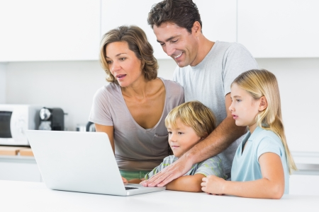 Happy family using laptop in kitchen photo
