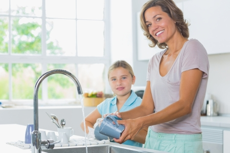 kitchen sink: Happy mother and daughter doing the washing up together in kitchen