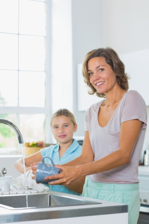 Mother washing up with daughter drying kitchen photo