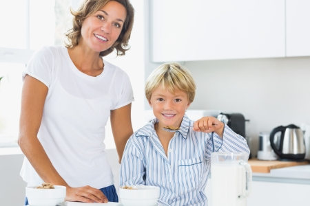 Mother and son having breakfast in kitchen photo